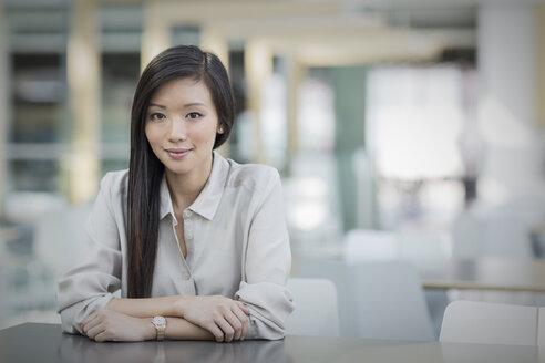 Portrait confident businesswoman at table - HOXF03223