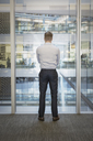 Businessman standing at office window overlooking atrium - HOXF03229
