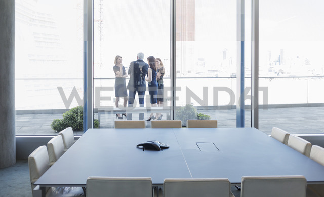 Business people talking on conference room balcony - HOXF03232