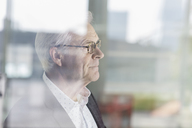 Pensive senior businessman looking out office window - HOXF03238