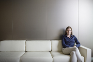 Portrait confident businesswoman with legs crossed on sofa - HOXF03244