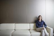 Portrait confident businesswoman with legs crossed on sofa - HOXF03244
