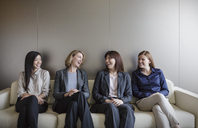 Smiling businesswomen talking in a row on sofa - HOXF03256