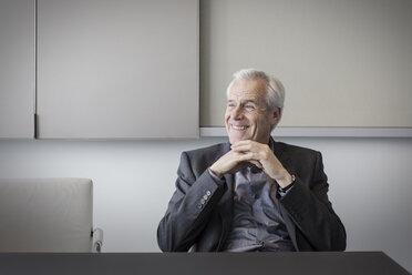 Smiling senior businessman looking away - HOXF03262