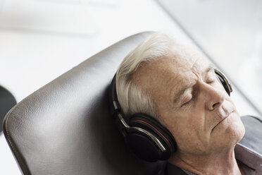 Senior man with headphones listening to music and reclining - HOXF03265
