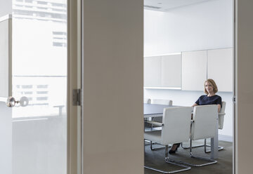 Portrait businesswoman waiting in conference room - HOXF03268