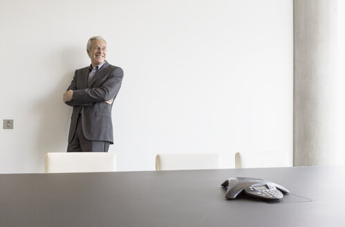 Smiling senior man looking away in conference room - HOXF03274