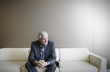 Senior man on sofa looking away - HOXF03277