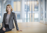 Portrait confident businesswoman leaning on conference table - HOXF03283