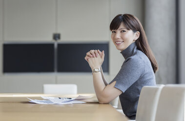 Portrait confident businesswoman with paperwork in conference room - HOXF03292