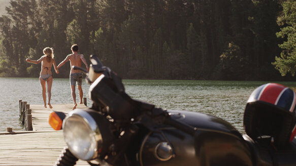 Young couple holding hands and running on lakeside dock behind motorcycle - HOXF03325