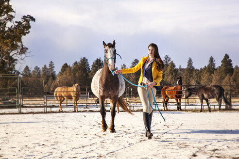Confident woman walking with horse on snow covered field - CAVF00007