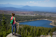 Female hiker looking at lake and trees while standing on top of cliff - CAVF00016