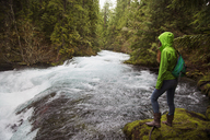 Female hiker standing by stream against trees at forest - CAVF00022