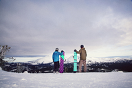 Friends holding snowboards while standing on snow covered field - CAVF00109