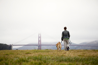 Rear view of woman and dog walking on grassy field at Golden Gate Park - CAVF00169
