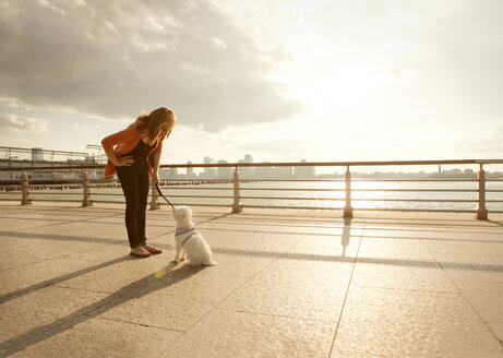 Woman looking at dog while standing by railing against sky on sunny day - CAVF00187
