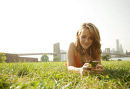 Smiling woman using smart phone while lying on grassy field against clear sky - CAVF00193