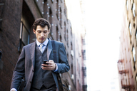 Low angle view of businessman using smart phone against buildings - CAVF00202