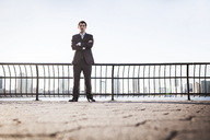 Low angle view of businessman standing against railing on sunny day - CAVF00211