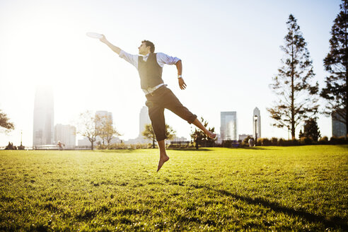 Businessman jumping and reaching plastic disk on grassy field - CAVF00214