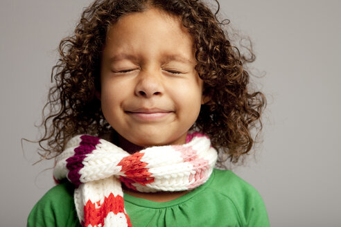 Close-up of cute girl with closed eyes against gray background - CAVF00289