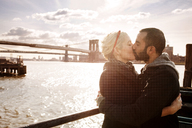 Couple kissing while standing against Brooklyn Bridge over East River on sunny day - CAVF00295