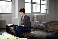 Businesswoman using laptop while sitting on sofa at creative office - CAVF00385