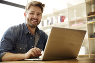 Portrait of happy man using laptop at home - CAVF00406