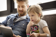 Girl looking at father using tablet computer while sitting on sofa at home - CAVF00412