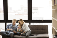 Family using tablet computer while sitting on sofa at home - CAVF00415