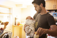 Father holding crying baby daughter in kitchen at home - CAVF00487