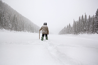 Rear view of man hiking on snow covered field - CAVF00595