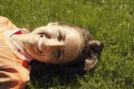 Close-up portrait of woman with dirty face lying on grassy field - CAVF00622