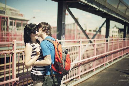 Man kissing girlfriend while standing at bridge on sunny day - CAVF00625