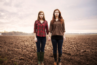Portrait of female friends holding hands while standing on field - CAVF00733