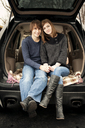 Portrait of happy young couple sitting car trunk - CAVF00745