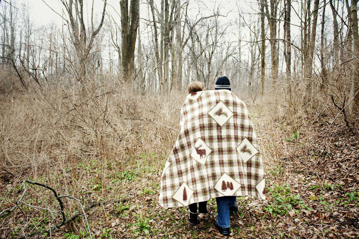 Rear view of couple wrapped in blanket while walking in forest - CAVF00748 - Cavan Images/Westend61