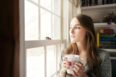 Thoughtful woman holding coffee mug while looking through window at home - CAVF00754