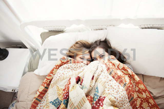 Overhead view of female friends pepping through blanket while lying on bed at home - CAVF00763 - Cavan Images/Westend61