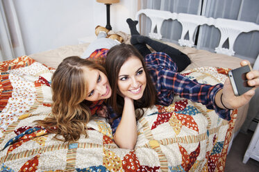 Happy friends taking selfie through smart phone while lying on bed at home - CAVF00766