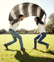 Couple playing under blanket in park during sunny day - CAVF00784