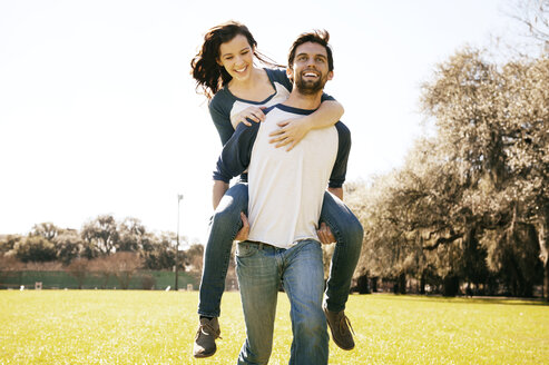 Man giving piggyback ride to woman at park - CAVF00790