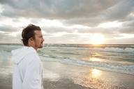 Side view of thoughtful man standing on beach against cloudy sky at sunset - CAVF00805