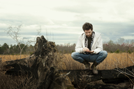 Man crouching on driftwood at field against cloudy sky - CAVF00808