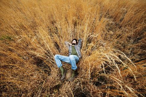 Overhead view of man lying on grassy field - CAVF00811