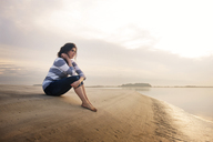 Thoughtful woman sitting on seashore against sky - CAVF00823