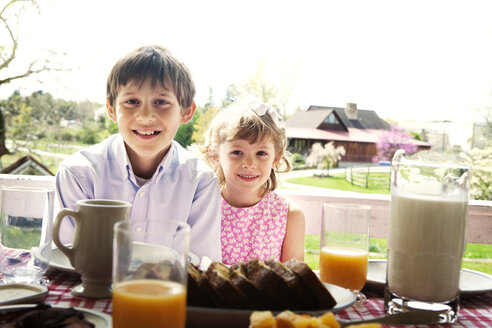 Portrait of siblings sitting at table during breakfast - CAVF00841