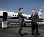 Happy businessmen doing handshake against corporate jet on runway - CAVF00856