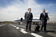 Happy businessmen walking on airport runway against sky - CAVF00859